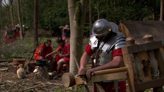 roman soldiers build tools and weapons at a forest campsite. - historical reenactment stock-videos und b-roll-filmmaterial