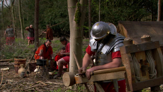 vídeos de stock, filmes e b-roll de roman soldiers build tools and weapons at a forest campsite. - reconstituição histórica