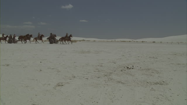 vídeos de stock, filmes e b-roll de roman soldiers charging across a snow covered desert on horses and chariots. - roman soldier