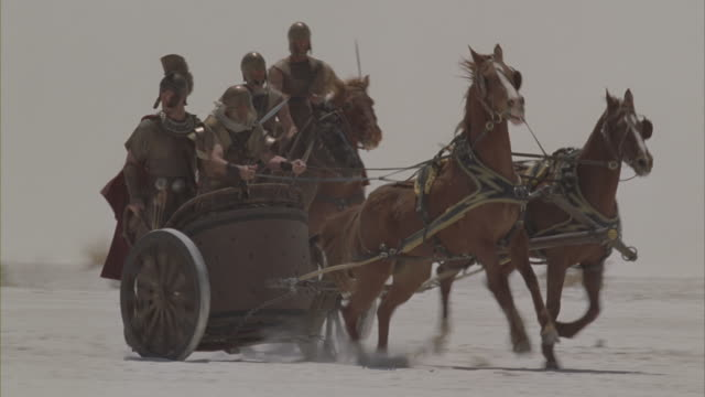 vídeos de stock, filmes e b-roll de roman soldiers charging across a snowy desert on horses and chariots. - roman soldier