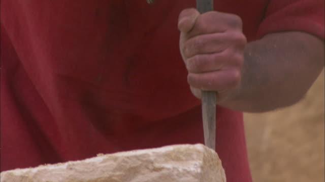 stockvideo's en b-roll-footage met roman soldiers chisel blocks of stone. - steengroeve