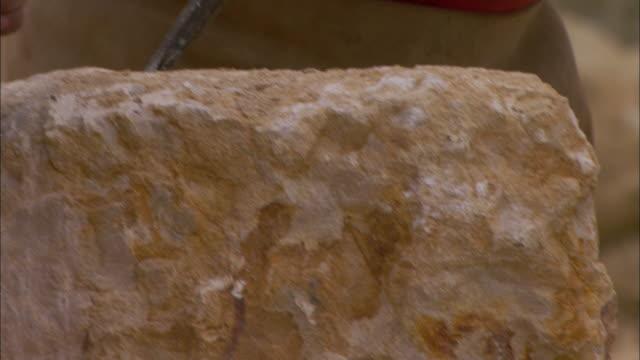 vídeos y material grabado en eventos de stock de roman soldiers chisel stones at a quarry. - piedra roca