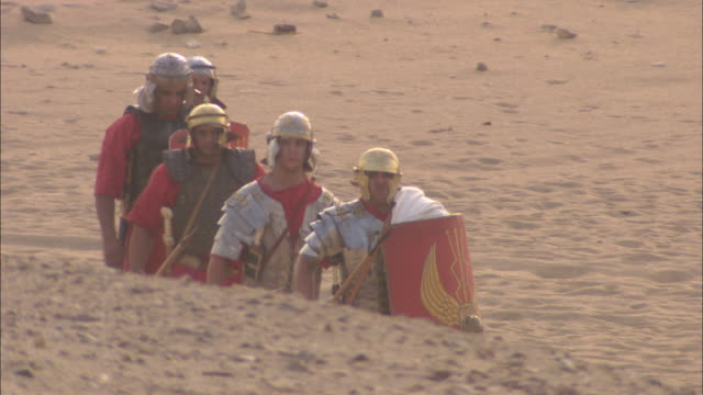 roman soldiers march across a dry field. - historische nachstellung stock-videos und b-roll-filmmaterial