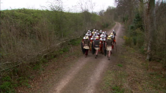 roman soldiers march in formation along a country trail. - traditional helmet stock videos and b-roll footage