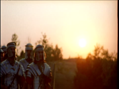 Roman soldiers pass by on dusty road at sunset Hungary