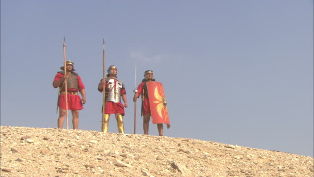 Roman soldiers stand on a hill.