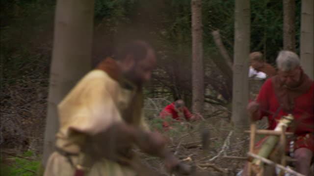 vídeos y material grabado en eventos de stock de roman soldiers use hand tools as they work at a forest campsite. - soldado romano