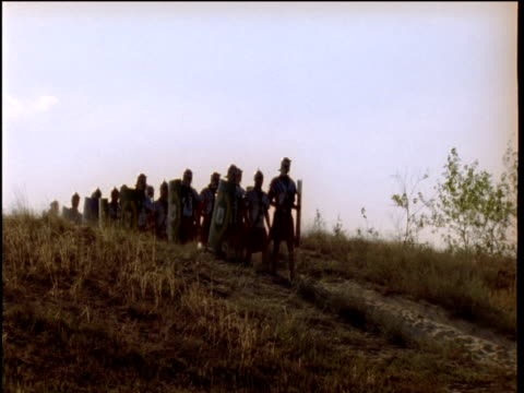 roman troops crest hill and march past hungary - römisch stock-videos und b-roll-filmmaterial