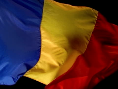 romania country flag flying against black bg. three vertical bands blue, yellow red. - romania stock videos & royalty-free footage