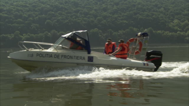 a romanian border police motorboat forms a wake as it speeds past. - flytväst bildbanksvideor och videomaterial från bakom kulisserna