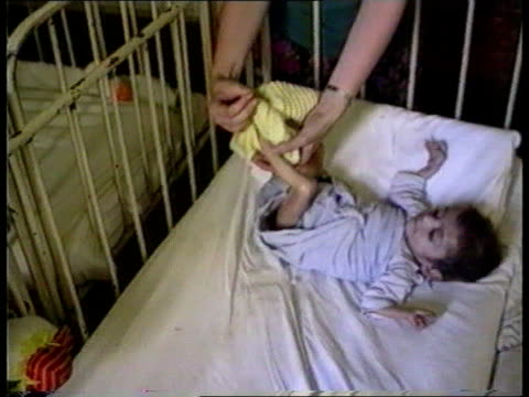 Glen Oglaza ITN /ITN TMS Child in cot in AIDS ward CMS Sick child held CMS Wound on leg MS Same child held TMS Child in cot as nurse removes its...