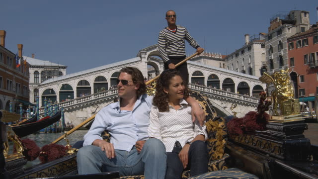 MS, Romanic couple in gondola, Rialto Bridge in background, Venice, Italy