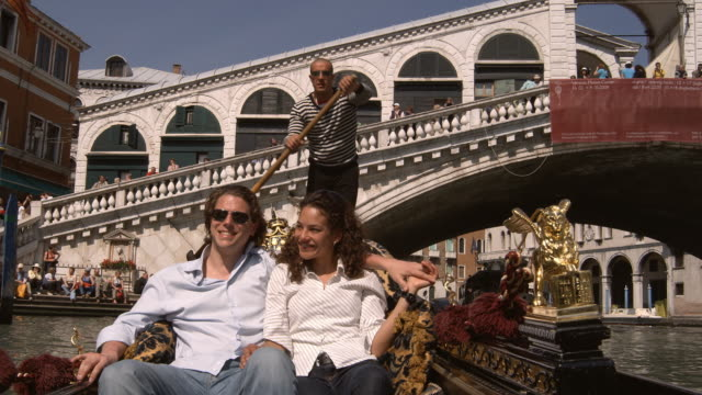 MS, Romanic couple in gondola, Rialto Bridge in background, Venice, Italy