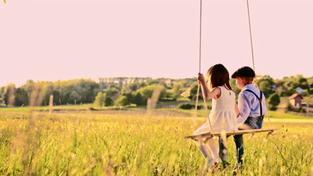 slo mo romantic boy and girl swinging on a tree swing - rope swing stock videos & royalty-free footage