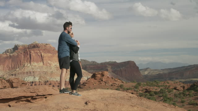 romantic couple admiring scenic view of desert landscape / capitol reef national park, utah, united states - top garment stock videos & royalty-free footage