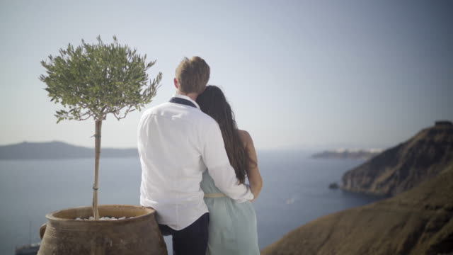 romantic couple beside little olive tree on santorini island - insel santorin stock-videos und b-roll-filmmaterial