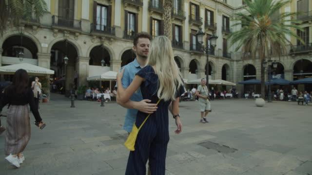 vídeos de stock e filmes b-roll de romantic couple dancing and kissing in urban plaza / barcelona, barcelona, spain - patio