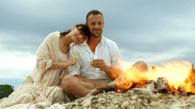 Romantic couple drinking champagne on the beach