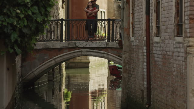 ws tu romantic couple embracing on footbridge over canal / venice - venedig stock-videos und b-roll-filmmaterial