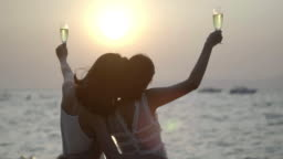 Romantic Couple Enjoying Sunset on Beautiful Tropical Beach.Pretty girl has a fun with her girlfriend on the beach.traveling in asia, summer vacation.LGBT Vacation,LGBT concept.