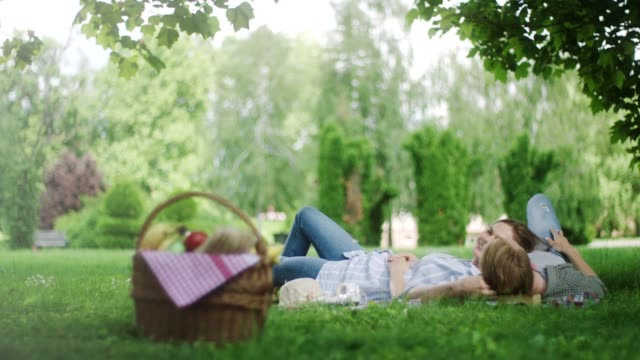 romantic couple enjoying time spent together on picnic in the nature - picnic basket stock videos & royalty-free footage