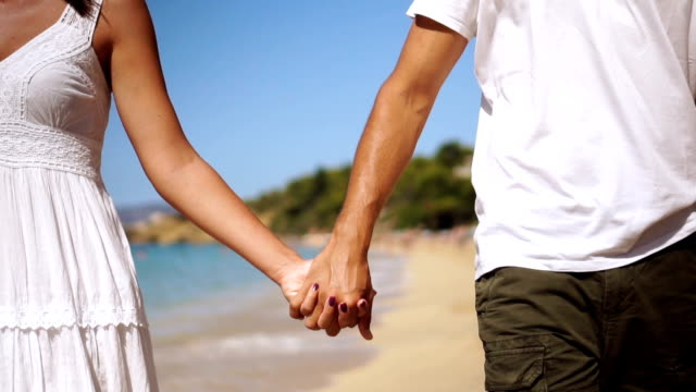 romantic couple holding hands on the beach - honeymoon stock videos & royalty-free footage