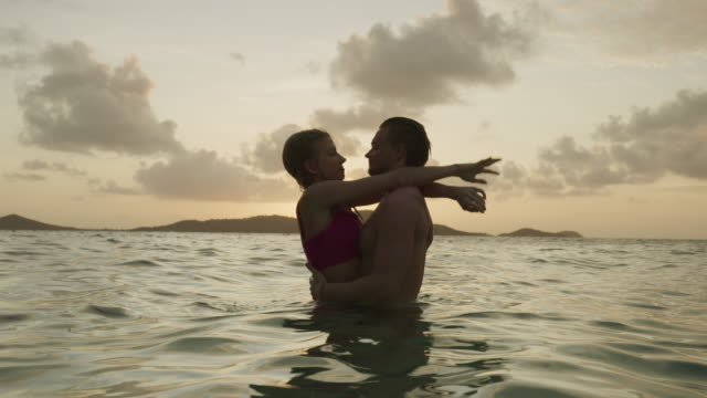 romantic couple hugging and kissing in ocean at sunset / jamesby island, tobago cays, st. vincent and the grenadines - camminare nell'acqua video stock e b–roll