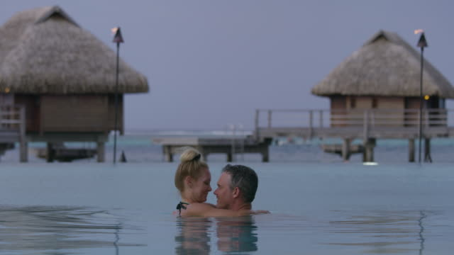 romantic couple hugging and kissing in ocean near bungalows in tahiti / moorea, french polynesia - moorea stock videos and b-roll footage