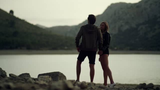 romantic couple hugging in mountains. sunset - romantic sky stock videos & royalty-free footage