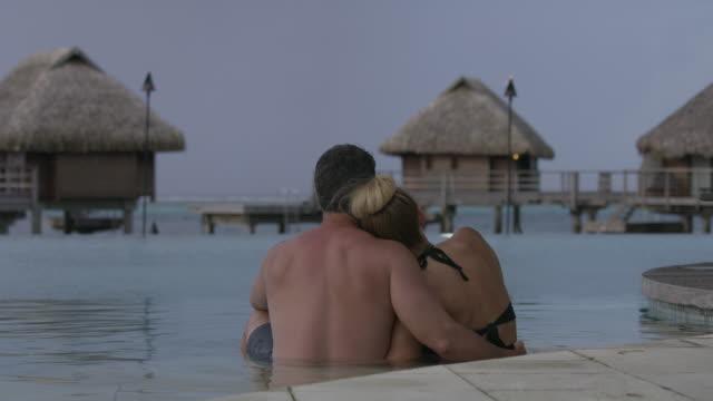 romantic couple hugging in ocean near bungalows in tahiti / moorea, french polynesia - tahiti stock videos & royalty-free footage