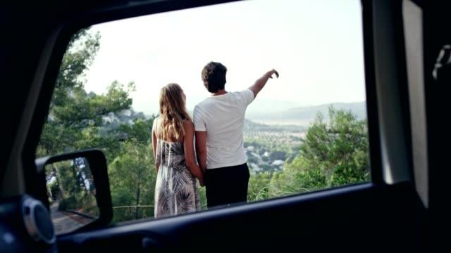 ロマンチックなカップルは岩の多い海岸線を抱き締めます。晴れた日 - 喜び点の映像素材/bロール