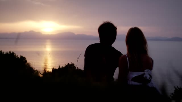 romantic couple hugging on rocky coastline. sunset - romantic sky stock videos & royalty-free footage