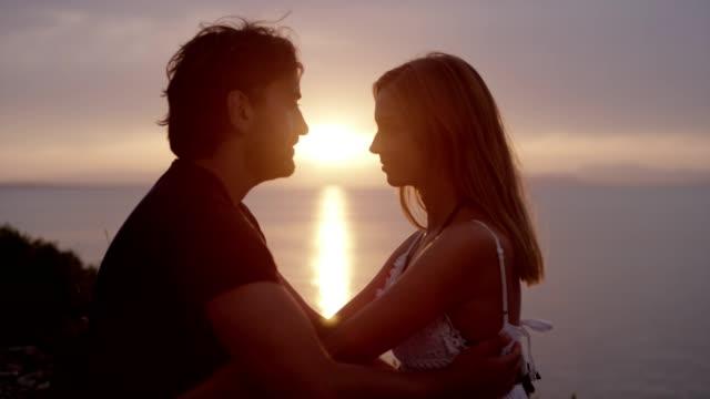 vídeos de stock, filmes e b-roll de casal romântico abraçando na costa rochosa. pôr do sol - amor à primeira vista