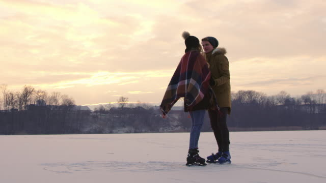 4k romantic couple ice skating and kissing on frozen lake, slow motion - ice skating stock videos & royalty-free footage