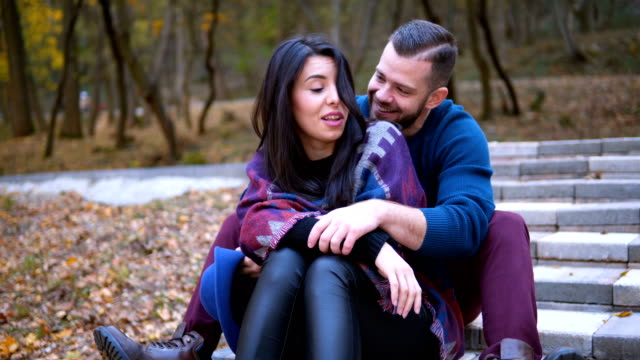 romantic couple in love sitting on stairs in park - andare giù video stock e b–roll