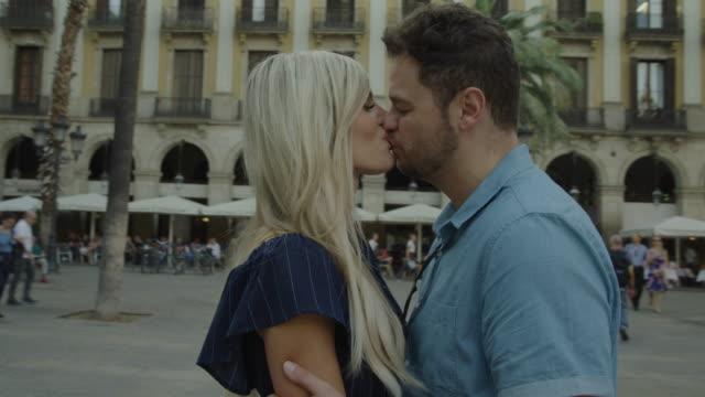 vídeos de stock, filmes e b-roll de romantic couple kissing in urban plaza / barcelona, barcelona, spain - casal jovem