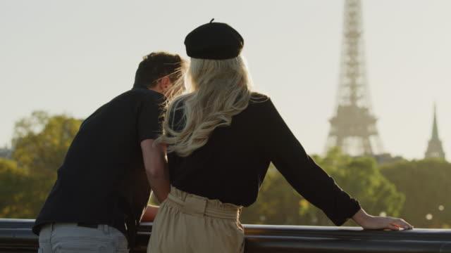 romantic couple kissing on pont alexandre near eiffel tower / paris, ile de france, france - baciare video stock e b–roll