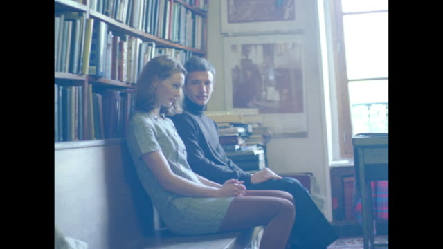 stockvideo's en b-roll-footage met romantic couple on a wooden bench against a book shelf wall. - breedbeeldformaat