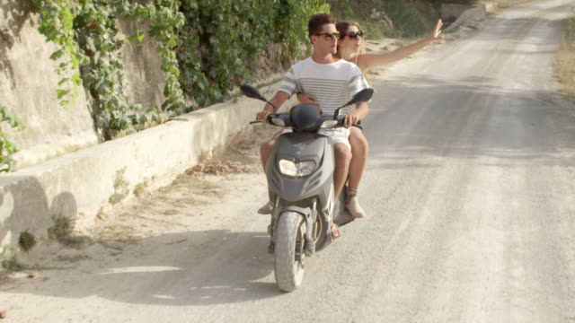 romantic couple on motor scooter - enjoying the journey