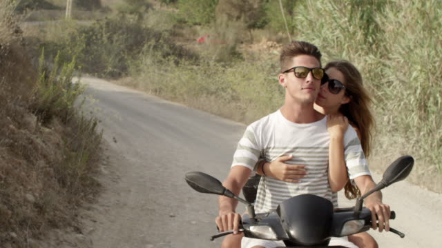 romantic couple on motor scooter- enjoying themselves and the road