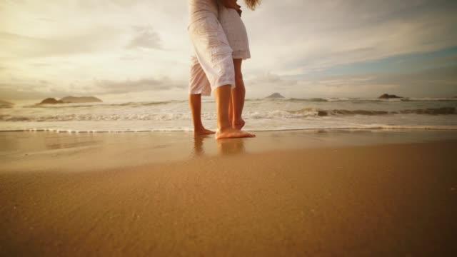coppia romantica sulla spiaggia ad un'alba colorata sullo sfondo - marito video stock e b–roll