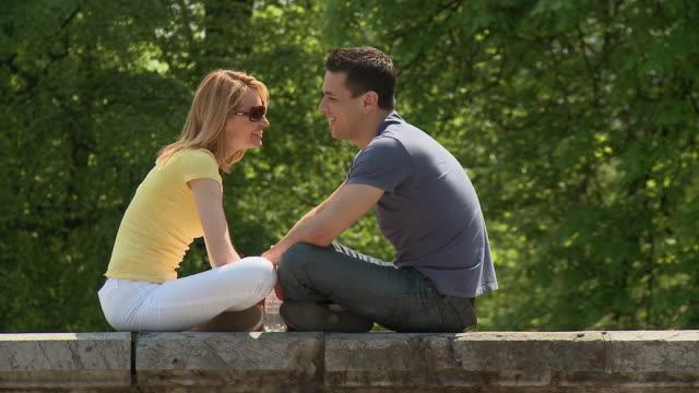 MS,  Romantic couple relaxing on wall in Park Tivoli, Ljubljana, Notranjska region, Slovenia