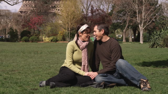 ws romantic couple sitting on lawn, talking and kissing / paris, france - hair accessory stock videos & royalty-free footage