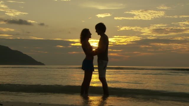 ws romantic couple standing in ocean waves at sunset / seychelles  - walking in water stock videos & royalty-free footage