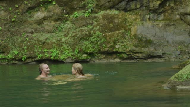 romantic couple swimming and kissing in river / carmel falls, grenada - キス点の映像素材/bロール