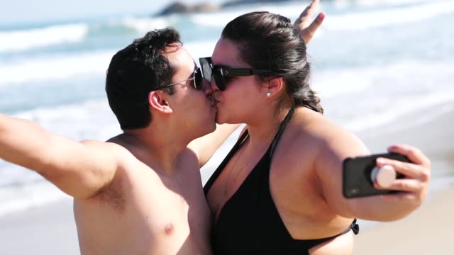 romantic couple taking a selfie on the beach - plus size model stock videos & royalty-free footage