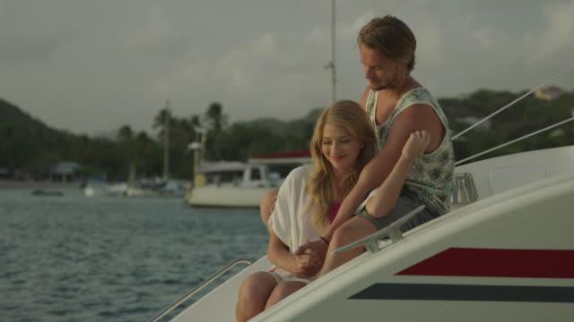 romantic couple talking and cuddling on catamaran / prickley bay, grenada - dreiviertelansicht stock-videos und b-roll-filmmaterial