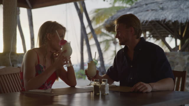 romantic couple toasting with cocktails at beach restaurant / salt whistle bay, mayreau, st. vincent and the grenadines - blondes haar stock-videos und b-roll-filmmaterial