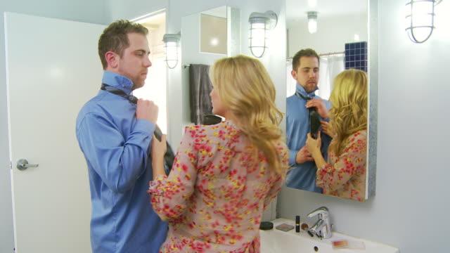 Romantic couple tying tie