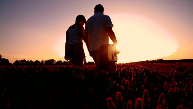 slo mo ロマンチックなカップルのお散歩の夕暮れ時の花 - 自由点の映像素材/bロール